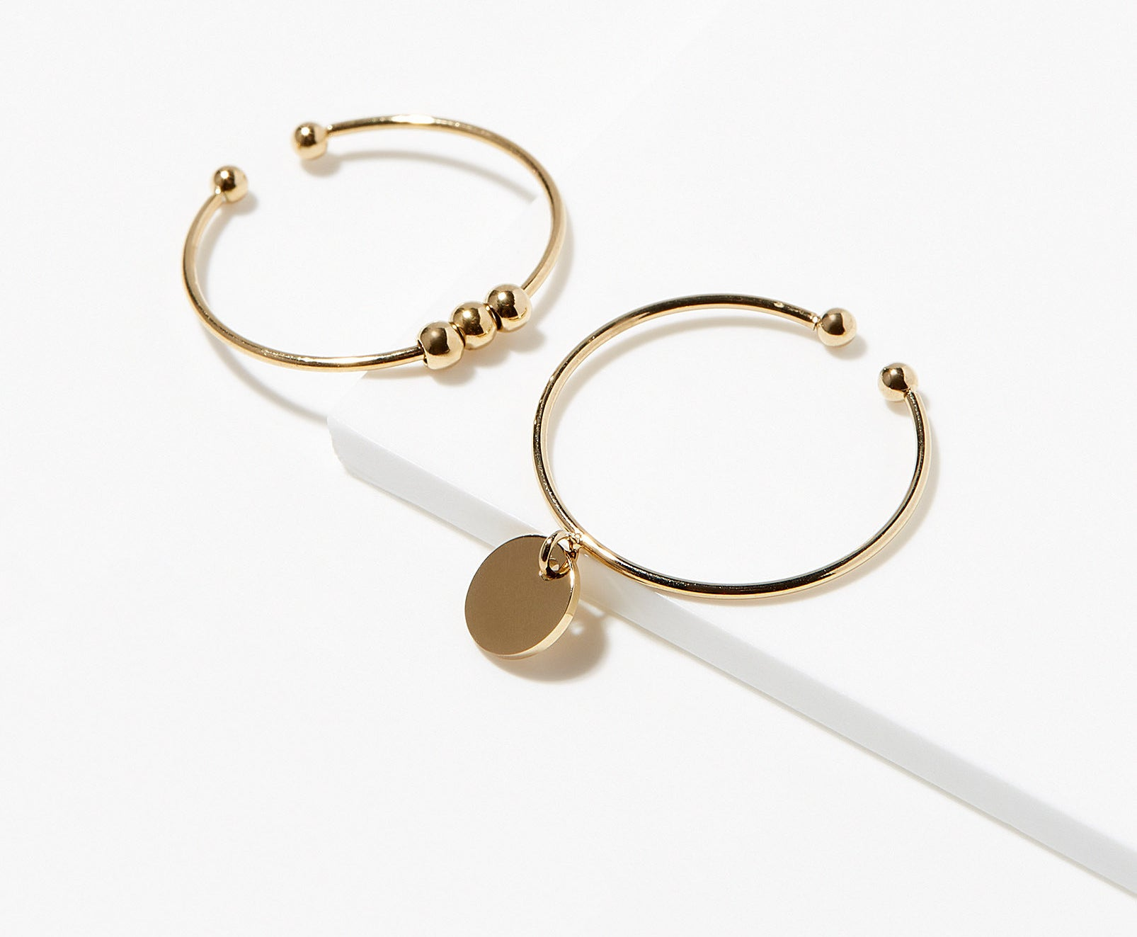 A pair of adjustable gold rings on a plain background