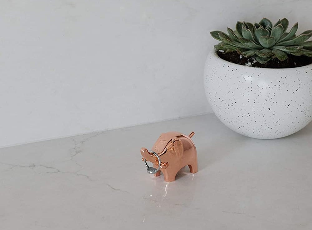 An elephant-shaped ring holder with a ring hanging from its trunk