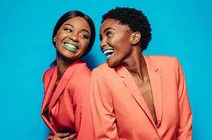 two women in matching burnt orange suits wearing green and blue lipstick while looking at each other smiling and laughing