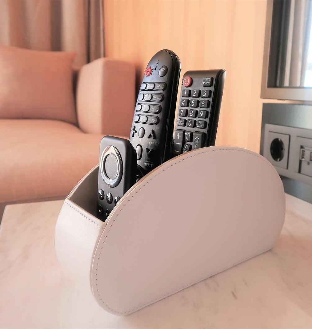 The off white leather remote organizer holding three remotes