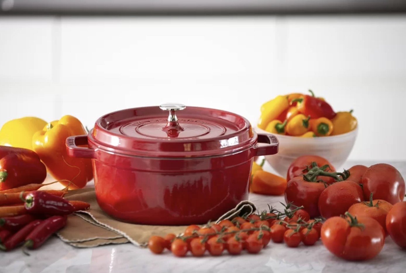 the dutch oven in red surrounded by vegetables