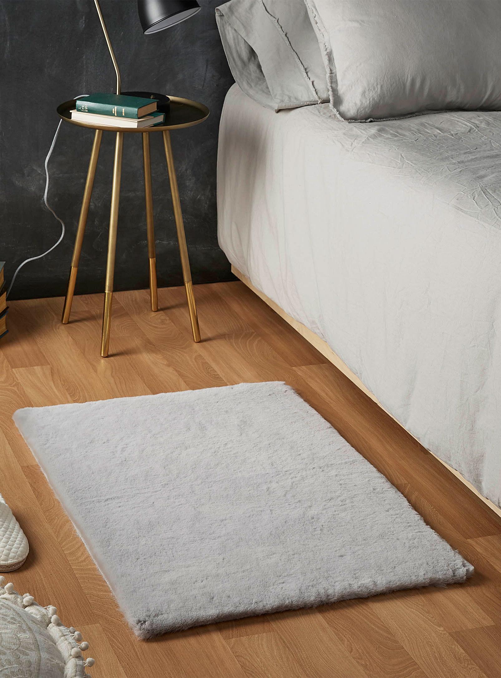 A faux fur rug on the floor near a bed