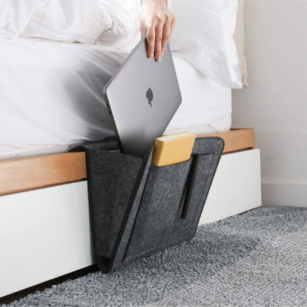 Someone slipping their mac book into the bedside caddy