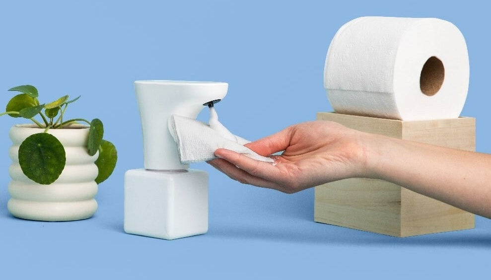A hand holding some toilet paper with foam on it under the Fohm dispenser next to a roll of toilet paper and a potted plant