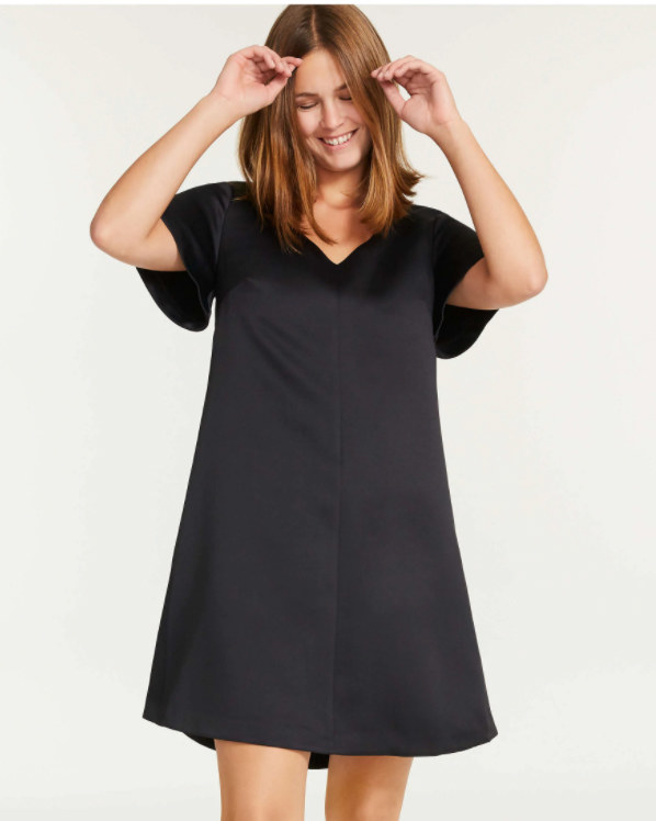 A person wearing a satiny T-shirt dress