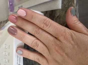 A reviewer's hand with gel nail polish in different shades of gray and pink
