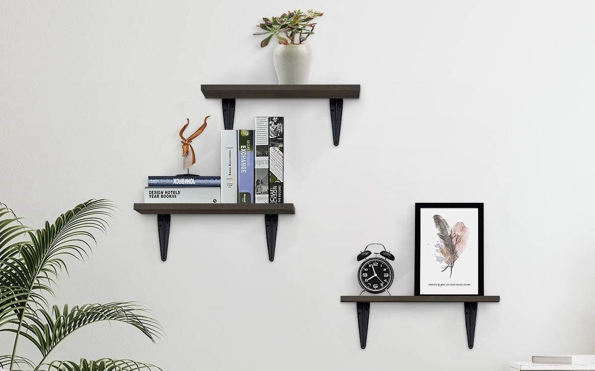 Three floating shelves with various items on them, like books, a clock, and artwork