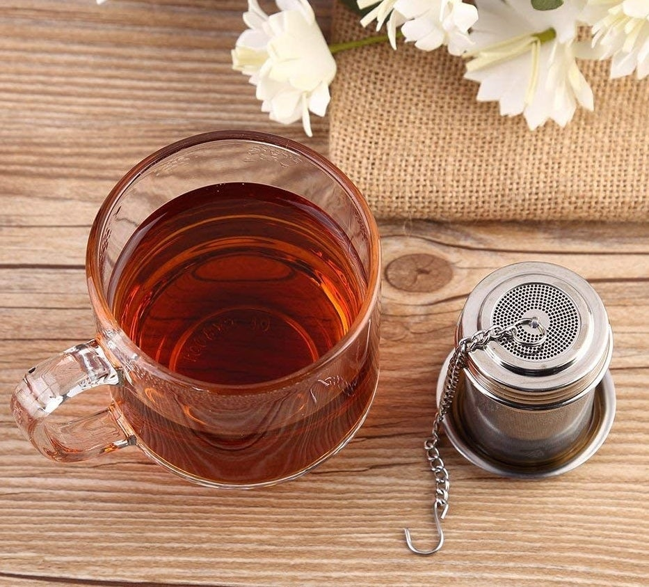 A clear mug of tea next to a stainless steel tea strainer with on a small corresponding saucer
