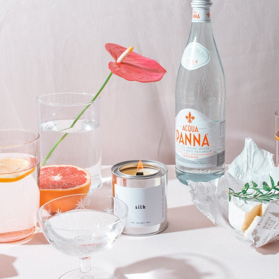 A lit candle in a metal tin with cups and of sparkling water beside it