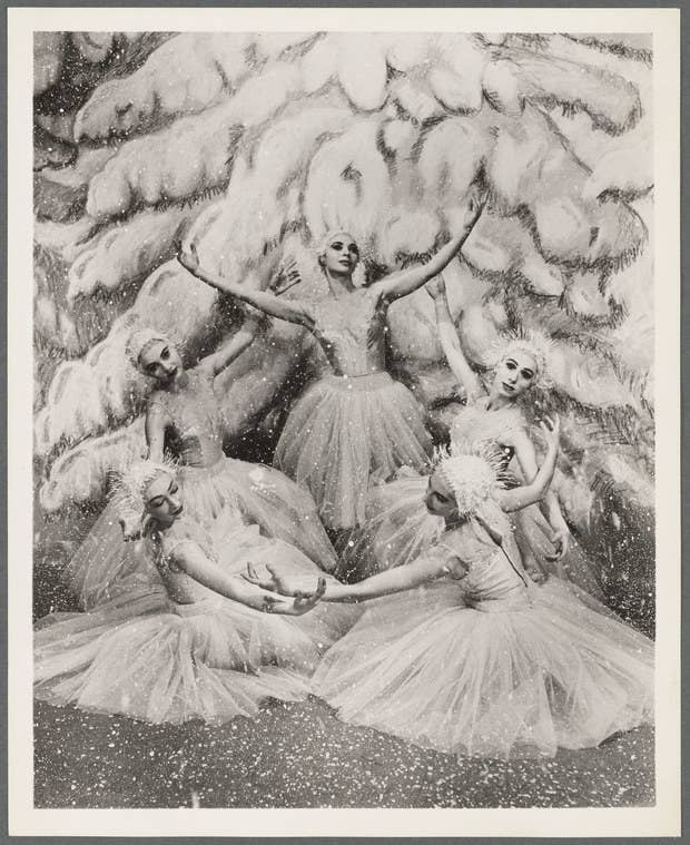 Women in ice costumes in front of a painted Christmas tree