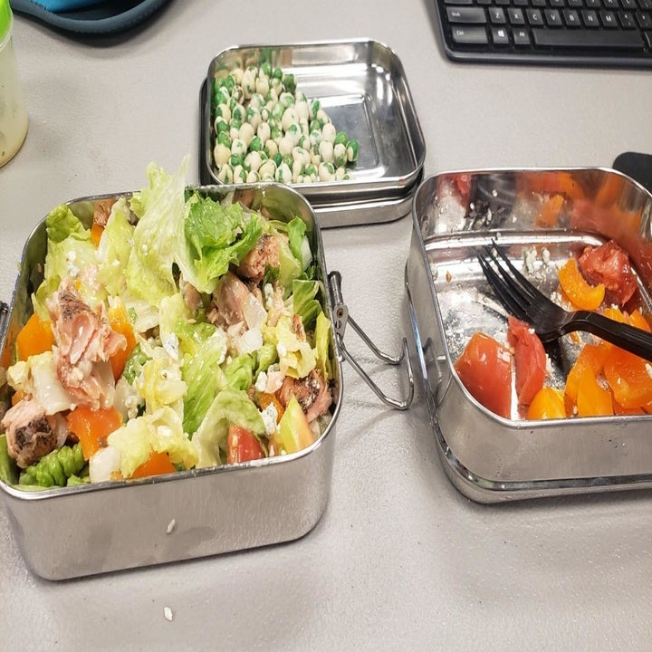 The stainless steel bento box taken apart to show food in the three stackable compartments