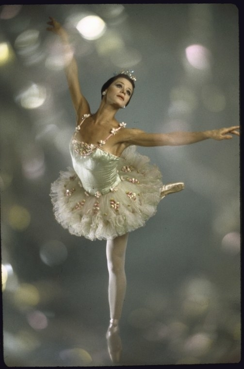 A ballerina in costume stands on one leg with glittering lights