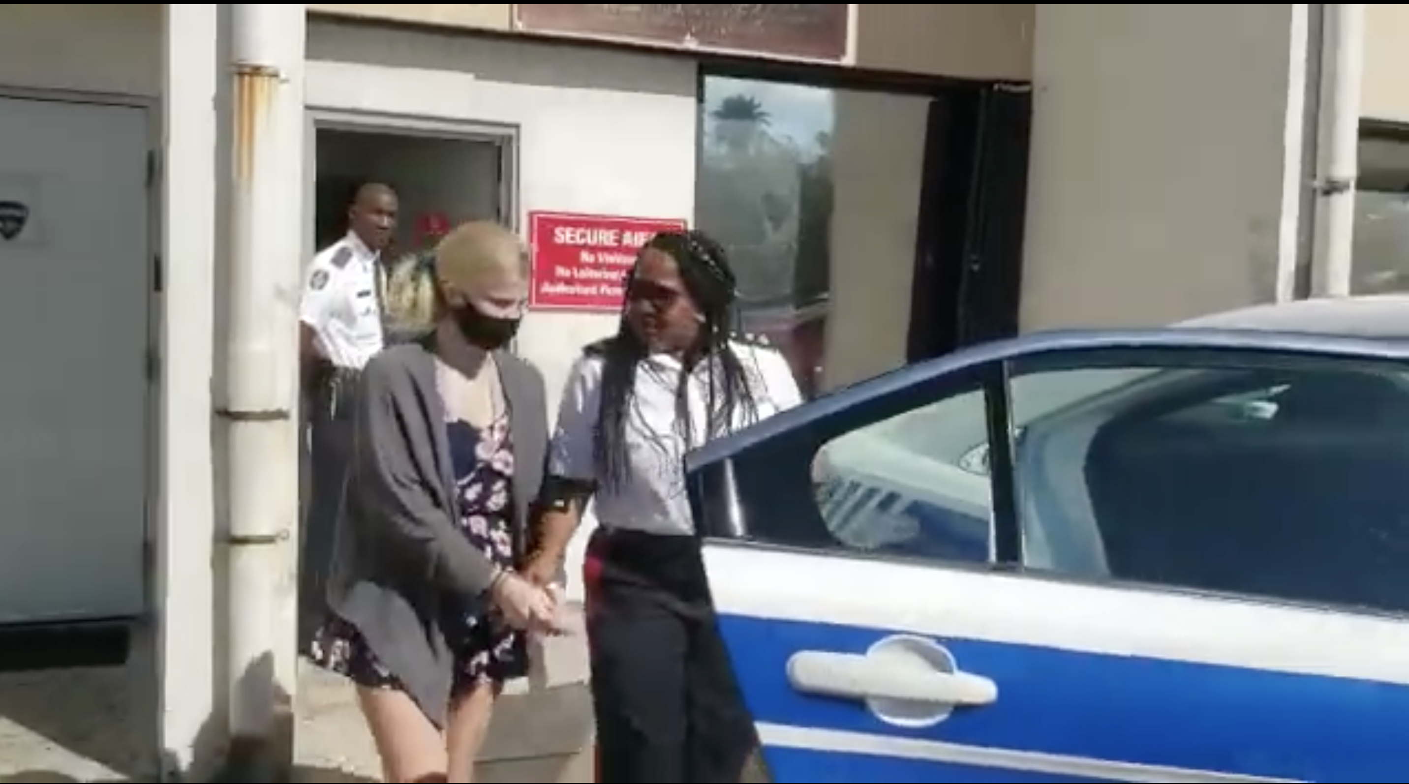 A police officer walks with Skylar Mack, handcuffed and wearing a face mask, to a police car