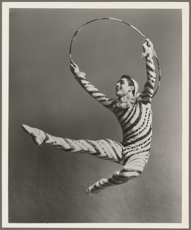 Man in a striped candy cane costume jumping with a hula hoop