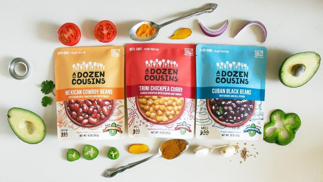 A Dozen Cousins Variety Pack in colorful pouches lined up next to veggies and spices