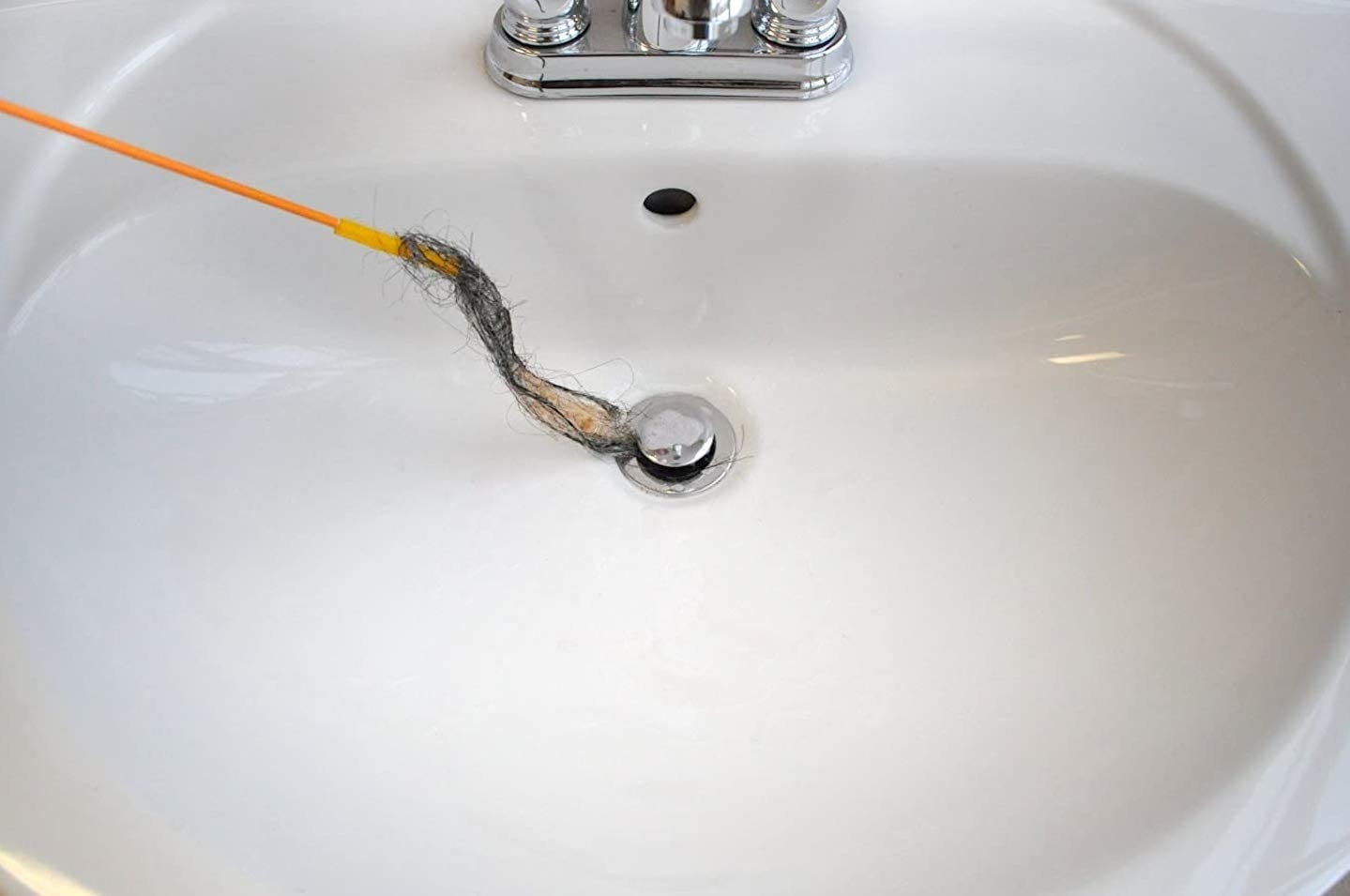 drain snake pulling out hair from a sink