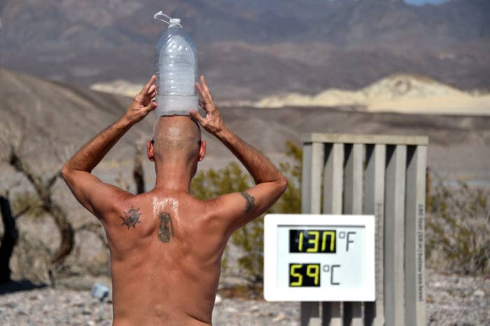 "A shirtless man sweats with a frozen gallon of water on his head, standing in front of a thermometer that reads ""130 degrees Fahrenheit, 59 degrees celsius"""