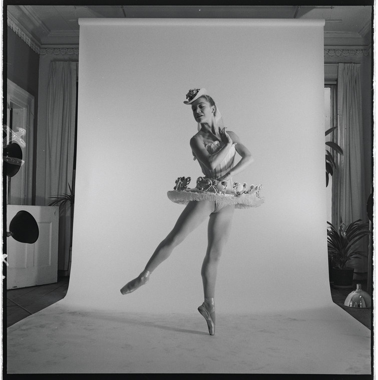 A woman ballerina in costume stands in front of a paper backdrop for a studio photo shoot