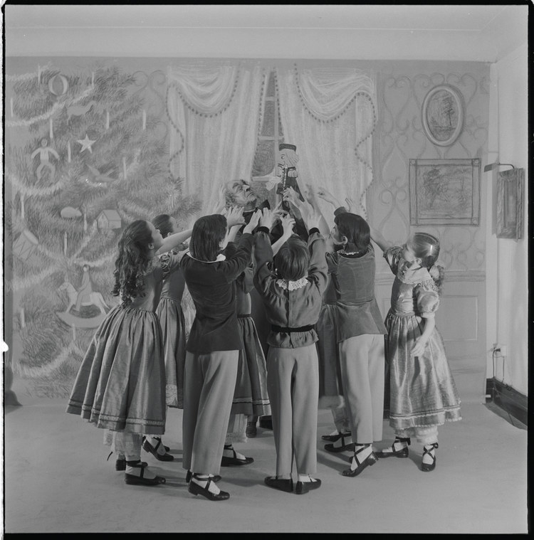 Children surrounding the old man and the Nutcracker on a dance set in front of a paper illustration of a living room with a Christmas tree decorated with garlands, ornaments, and candles