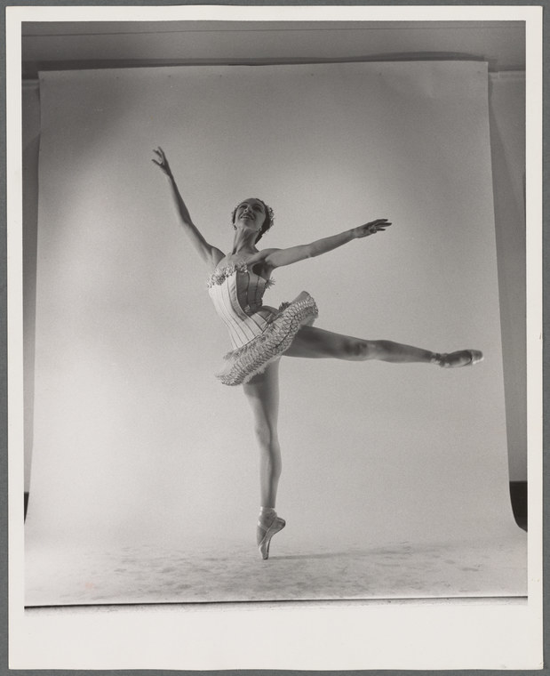 A ballet dancer wearing a frilly tutu with one leg raised