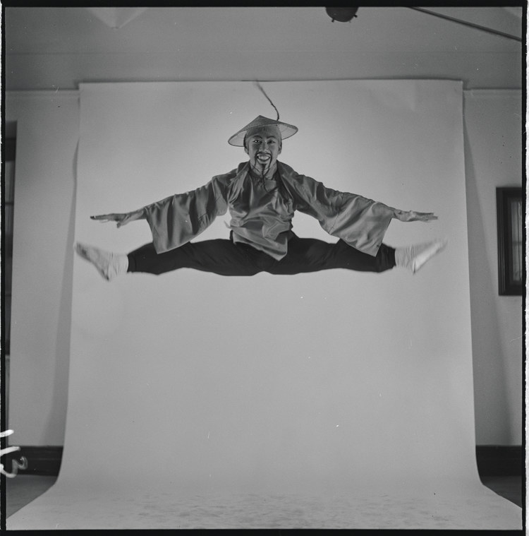 A man wearing a conical hat and sporting a long, fake mustache and goatee leaps in the air in front of a backdrop for a studio photo shoot