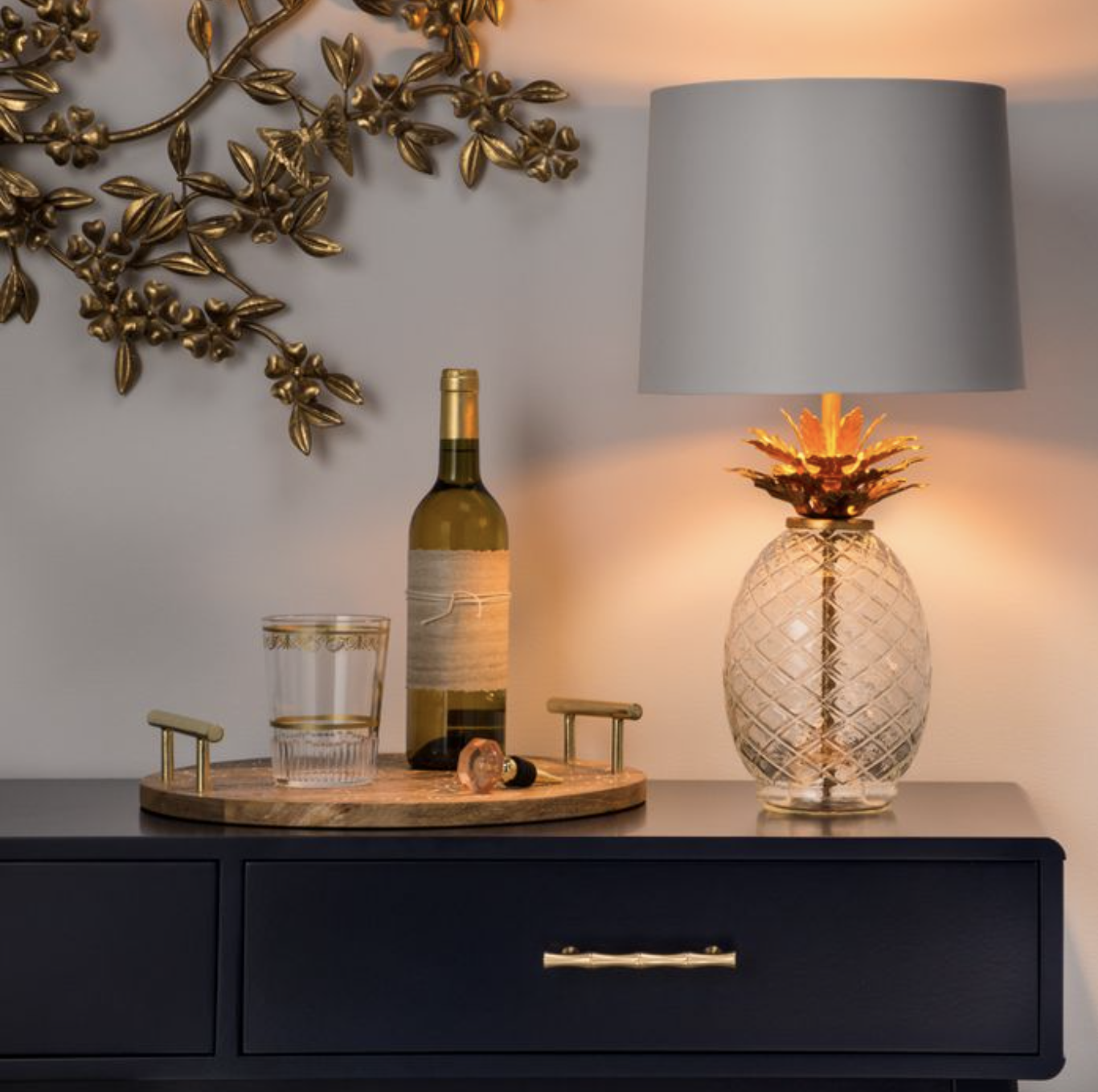 the glass pineapple table lamp on a credenza