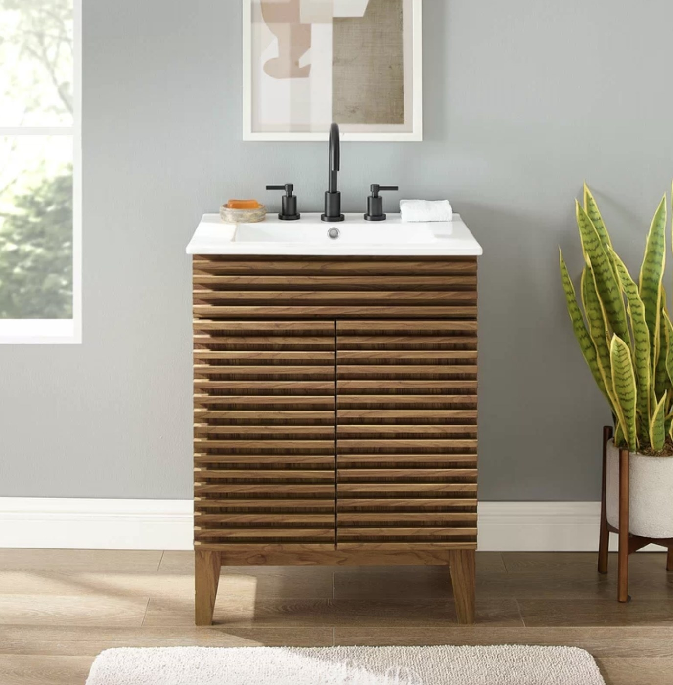 the vanity with a brown cabinet, white sink, and black faucet