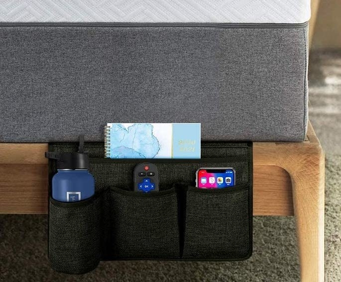 A bedside caddy with a waterbottle, journal, remote, and phone inside of it