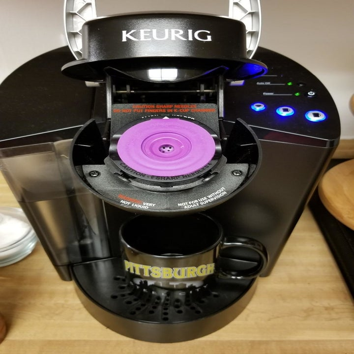 The same purple K-cup closed and inserted into a Keurig