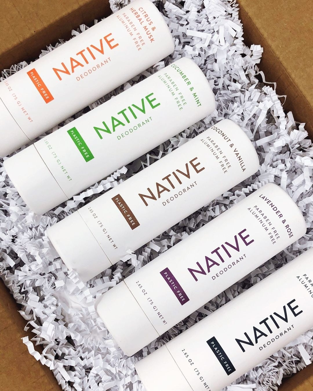 An open box filled with five Native deodorant sticks in different flavors and cardboard packaging