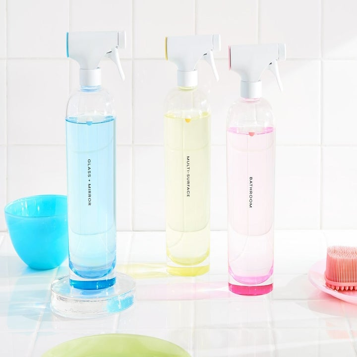 Three same three bottles filled with different-colored liquids that correspond to a colored tab on the spray bottle lidn