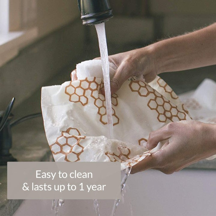 A model running the bees wrap under a sink faucet to clean