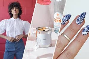 A person wearing a puffy-sleeved button up top, A lit candle in a metal tin on a table with glasses of sparkling water, A person with long painted nails that have intricately-designed flower stickers on them