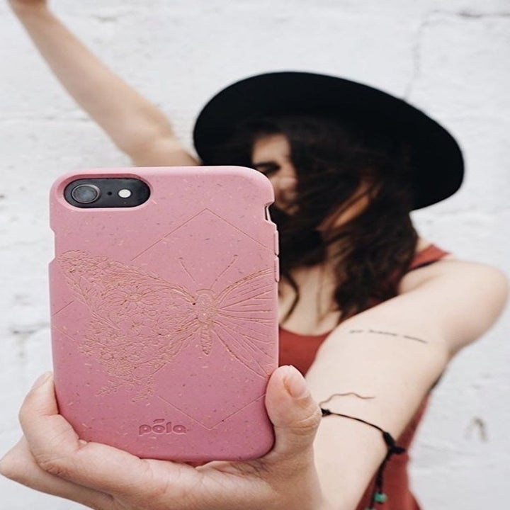 A model taking a selfie with an Android phone covered in a pink Pela case with a butterfly print