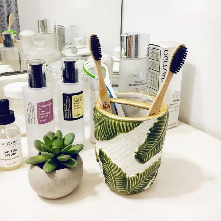 A reviewer photo of two bamboo toothbrushes in a leaf-printed cup on a bathroom countertop
