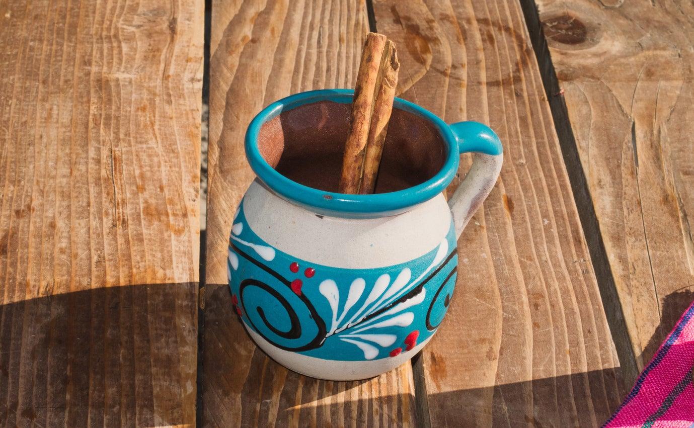 A close-up photo of a mug of champurrado with a cinnamon stick inside of it