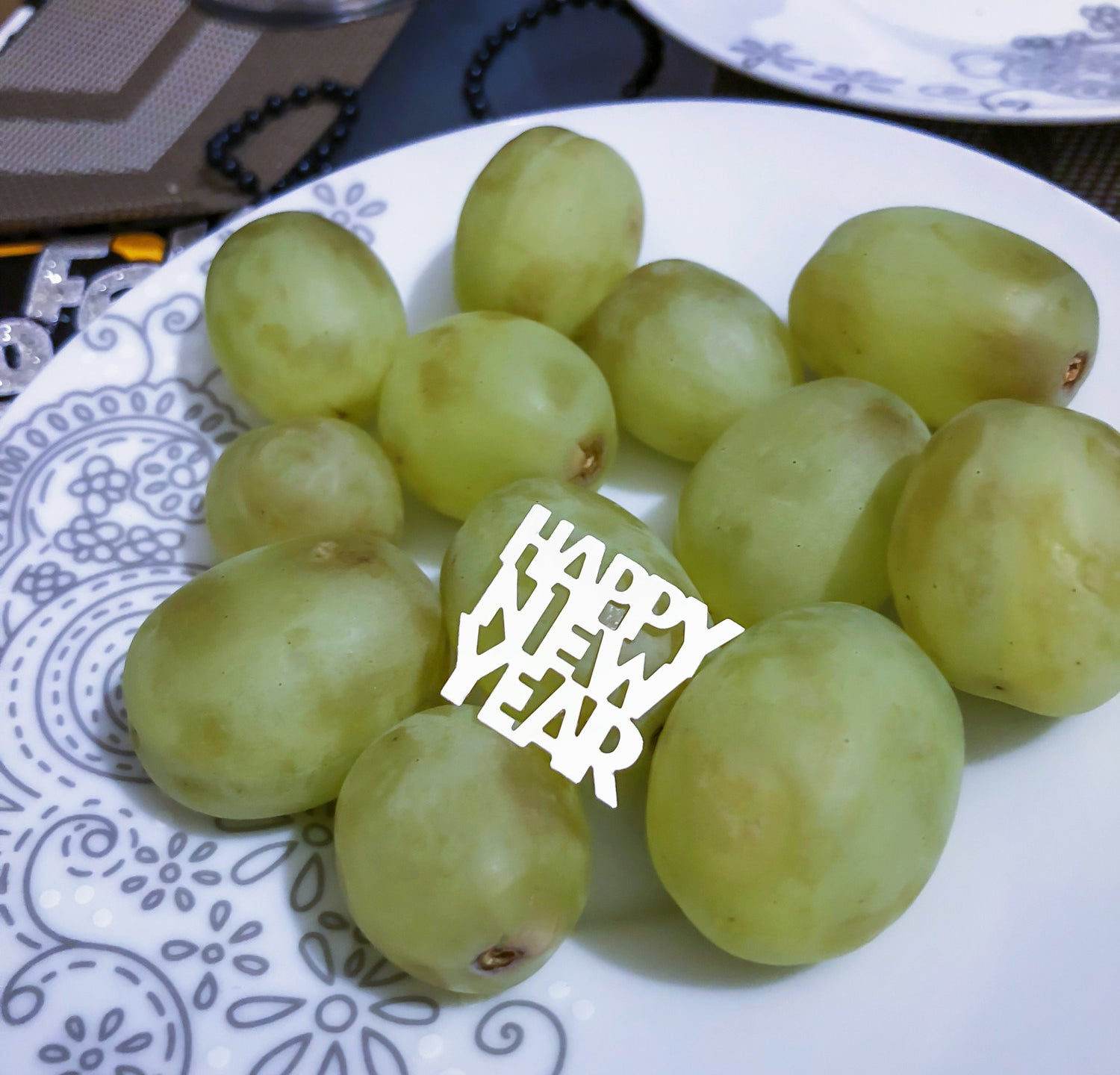 A photo of a dozen green grapes on a plate with a Happy New Year decoration on it