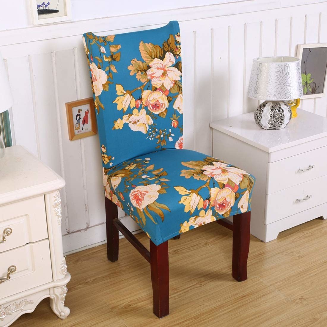 A chair covered in blue floral slip-on cover.