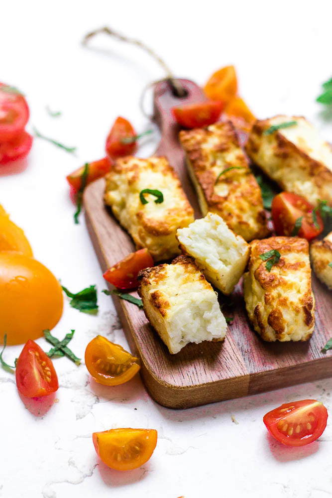 Slices of air fried halloumi cheese on a cutting board surrounded by tomatoes.