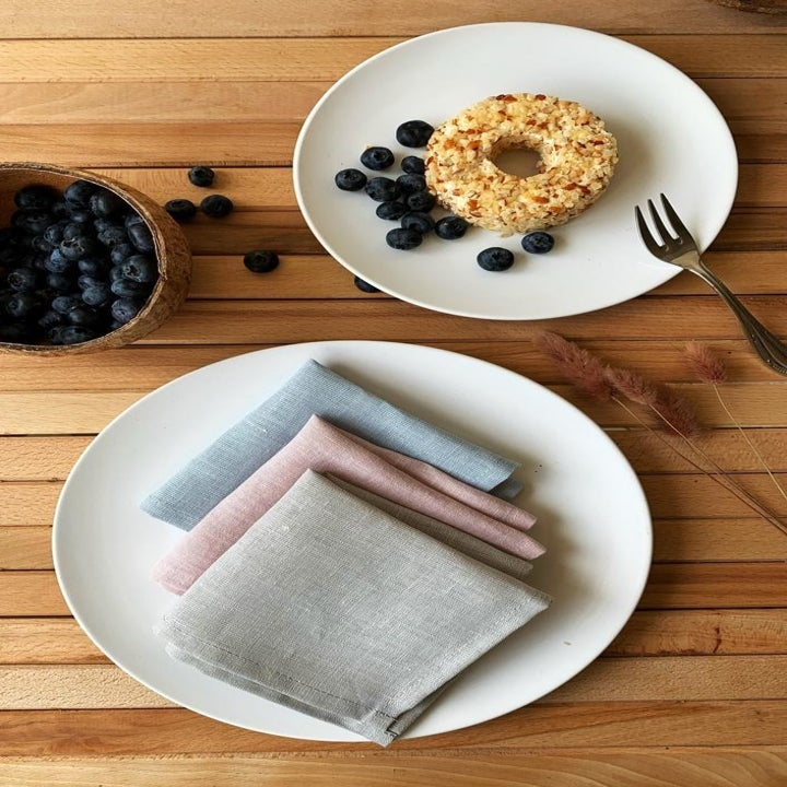 Three pastel-colored linen napkins sitting on a plate next to a bowl of blueberries and a bagel on another plate
