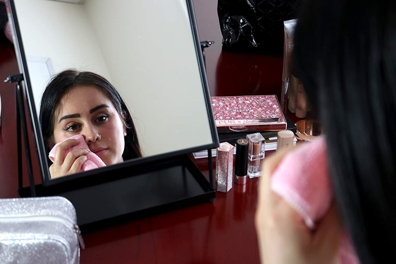 a person removing makeup in front of a vanity mirror with the microfiber cloth