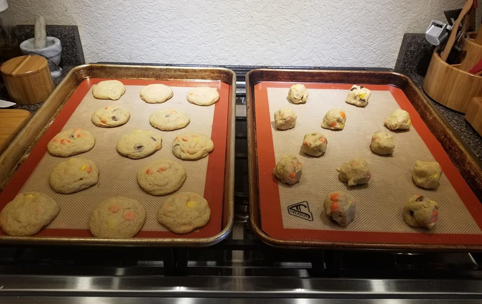 A reviewer photo of two baking sheets lined with the silicone mats and topped with baked cookies on one and balls of uncooked cookie dough on the other