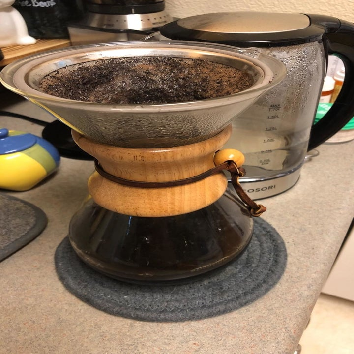 A reviewer photo of a glass pour-over coffee carafe with the reusable filter inserted in the top filled with coffee grounds and water