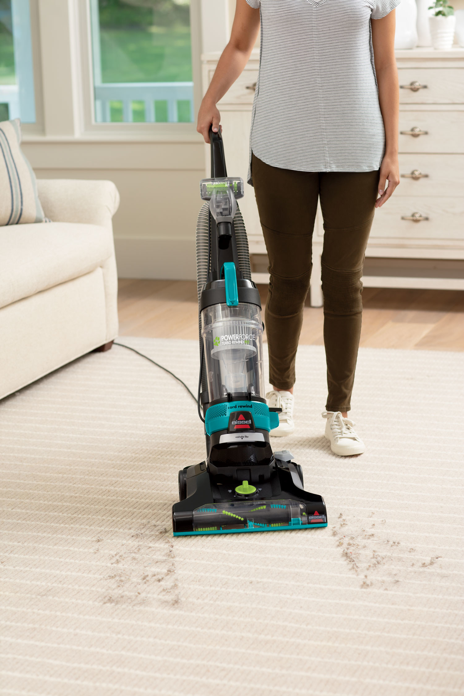 person using a bissell pet vacuum to suck up pet hair on the rug