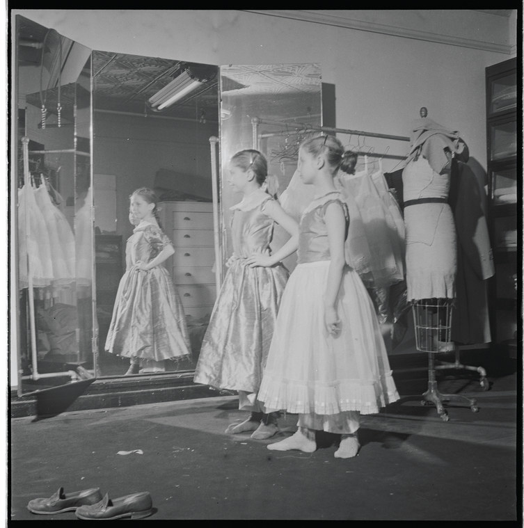 Two girls standing backstage next to a mirror with a mannequin behind them