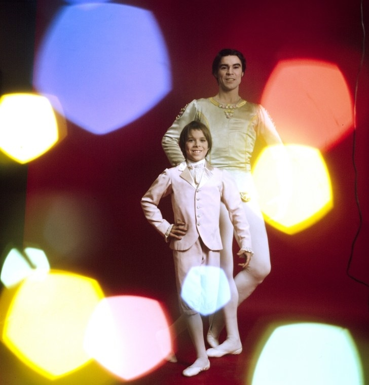 A man and boy make the same pose against a studio backdrop as colorful bokeh lights flash at the camera
