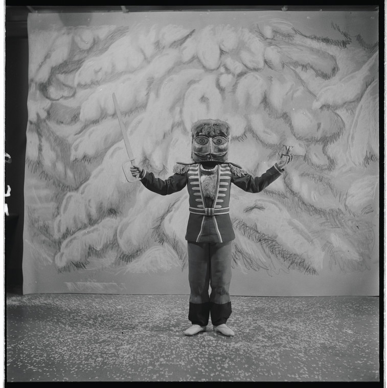 A boy in the Nutcracker costume holds a fake sword in front of a painted background