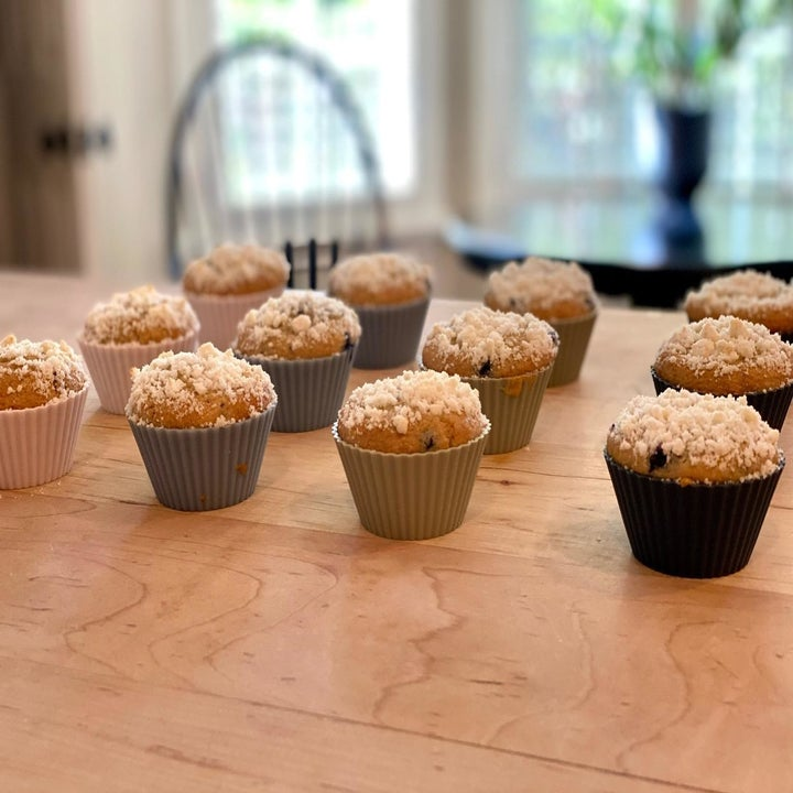 A reviewer photo of a bunch of muffins sitting on a countertop in the different-colored silicone baking cups