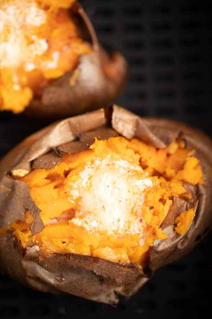 Two baked sweet potatoes topped with honey butter.