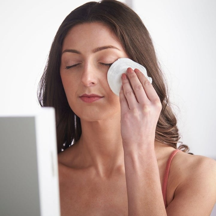A model using a reusable cotton pad on their face